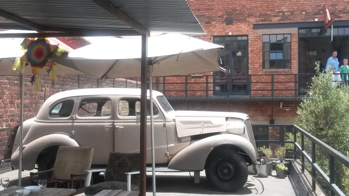An art-sy old car on the roof-top bar